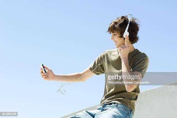 Teenage boy sitting outdoors, listening to headphones, looking at mp3 player, side view
