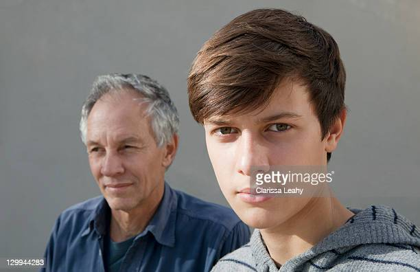 Teenage boy sitting with father