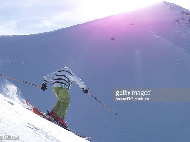 teenage boy skis down mountainside, sunset - bardonecchia stock photos and pictures
