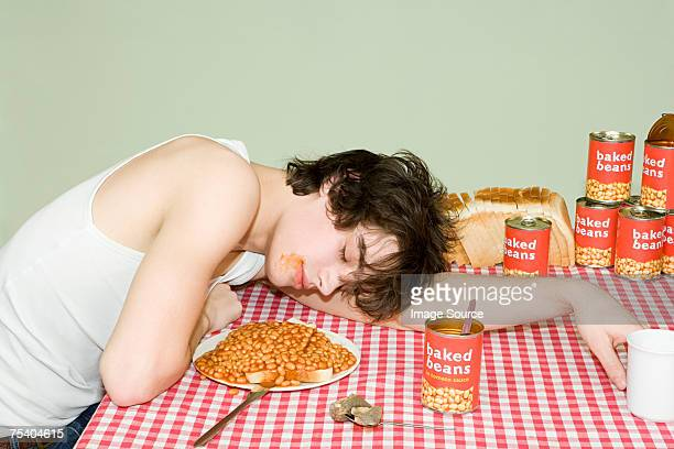Teenage boy sleeping near a plate of beans