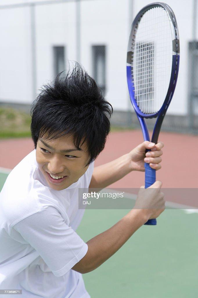 Teenage boy smiling and holding tennis racket : Photo