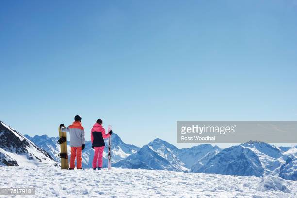 teenage boy snowboarder with sister skier looking out from snow covered mountain top, rear view,  alpe-d'huez, rhone-alpes, france - skiing stock pictures, royalty-free photos & images