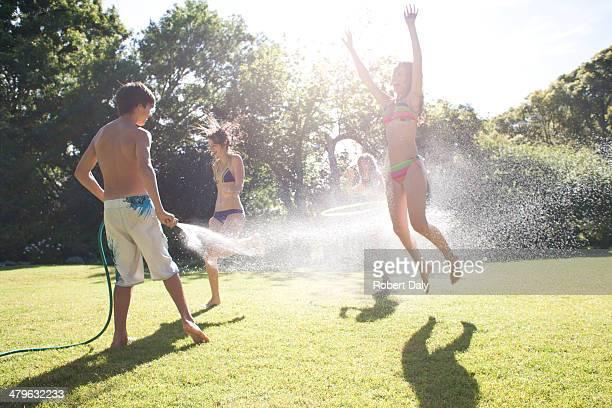 Teenager boy sprühen Teenager Mädchen mit Wasserschlauch im Freien
