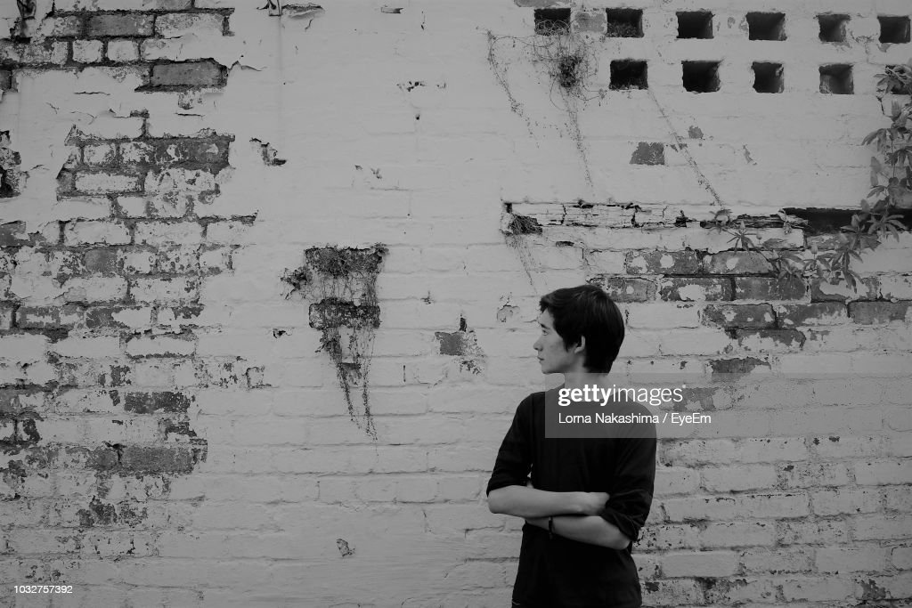 Teenage Boy Standing Against Weathered Wall : Stock Photo