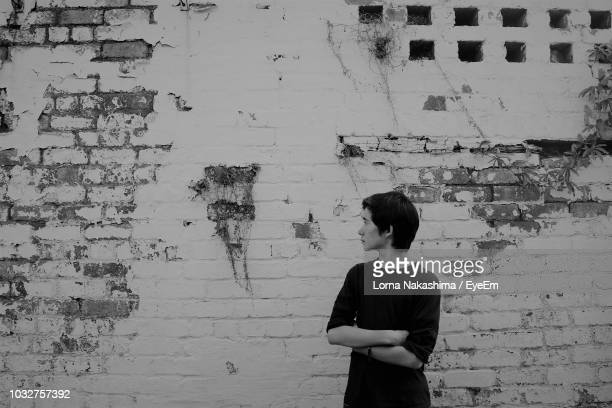 Teenage Boy Standing Against Weathered Wall