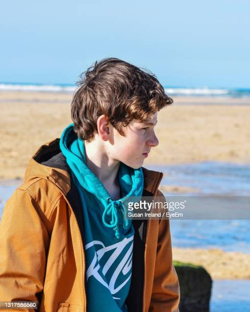 teenage boy standing at beach against sky - photo shoot stock pictures, royalty-free photos & images