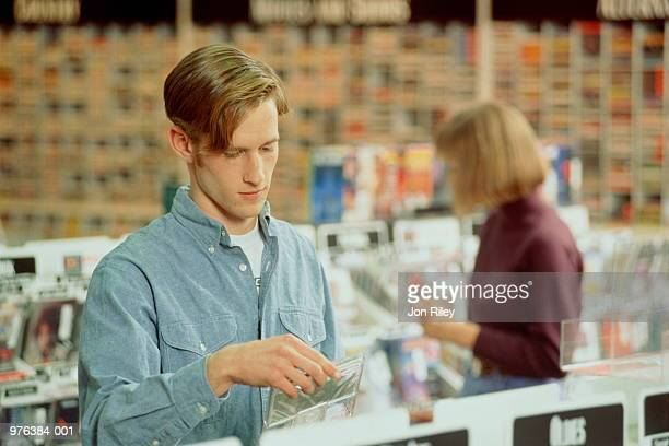 Teenage boy (16-18) standing between CD racks, holding CD case