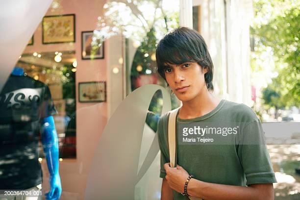 Teenage boy (16-18) standing by shop window, portrait