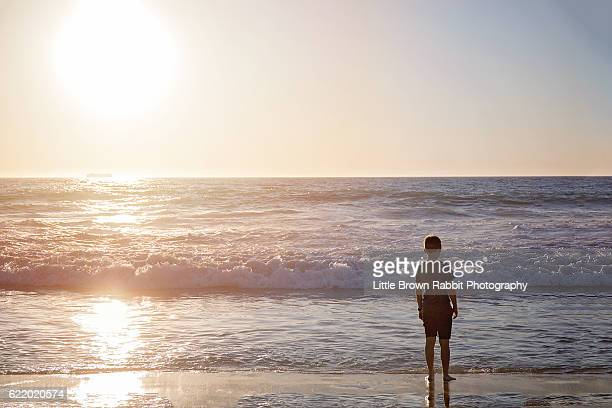 Teenage Boy Standing Contemplatively On the Shoreline Looking At The Ocean