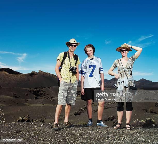 Teenage boy (14-15) standing in desert with parents, portrait