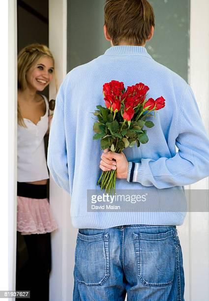 Teenage boy standing in doorway with roses behind his back, girl in background
