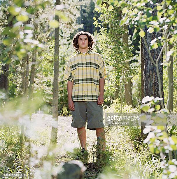 Teenage boy (16-18) standing in woods
