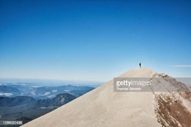 teenage boy standing on ridgeline at the top of mt st helens - paisajes de st thomas fotografías e imágenes de stock