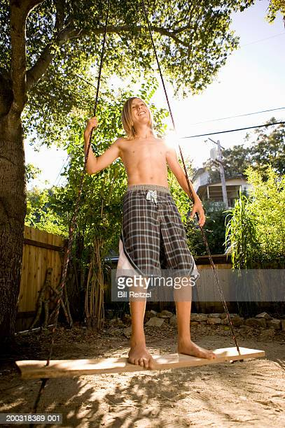 Teenage boy (13-15) standing on rope swing, smiling, low angle view