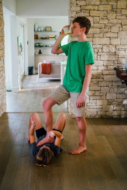 Teenage Boy Standing over Sister Drinking Glass of Milk