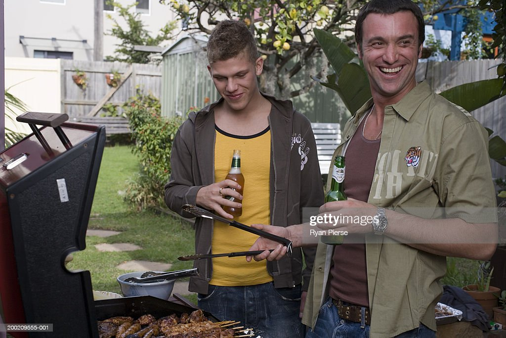 Teenage boy (16-18) standing with man tending barbecue : Stock Photo