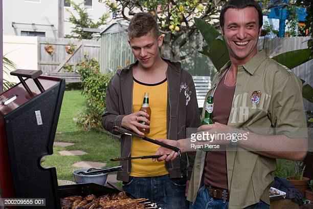 Teenage boy (16-18) standing with man tending barbecue