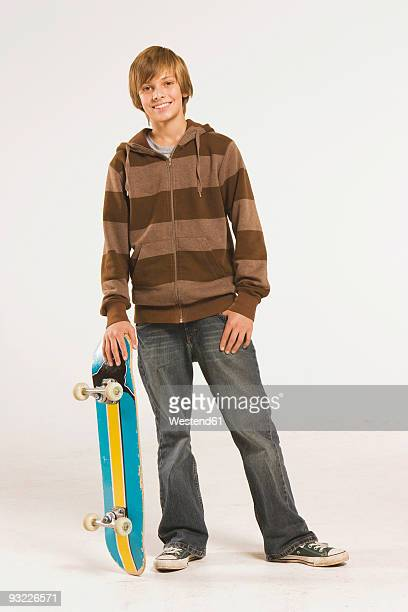 Teenage boy (14-15) standing with skateboard, smiling