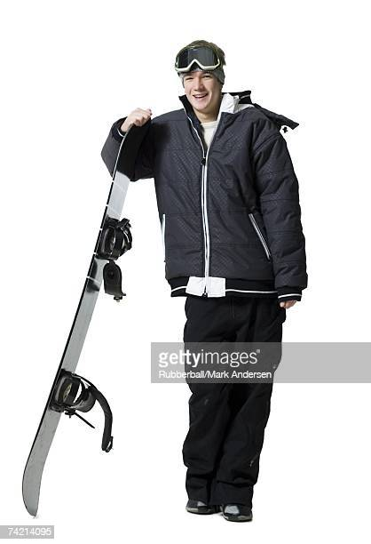Teenage boy standing with snowboard and goggles