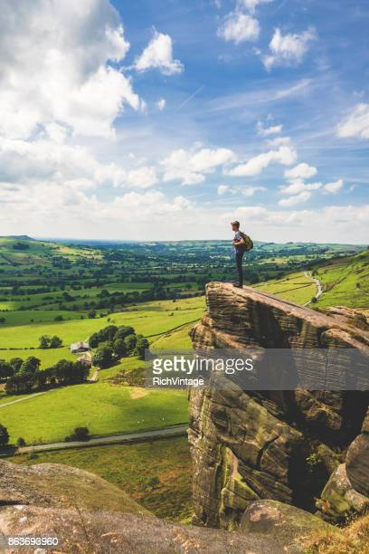 teenage boy stands at edge in peak district - england stock pictures, royalty-free photos & images