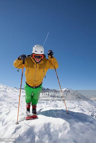 Teenage boy stands on ski tips, on ridge crest