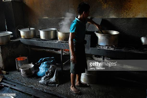 A teenage boy stirs a pot of curry in the kitchen of a teashop in downtown Mandalay Myanmar There are about 40 boys working in this teashop all from...