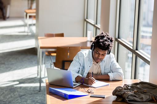 Teenage boy studies in school library 1137620178