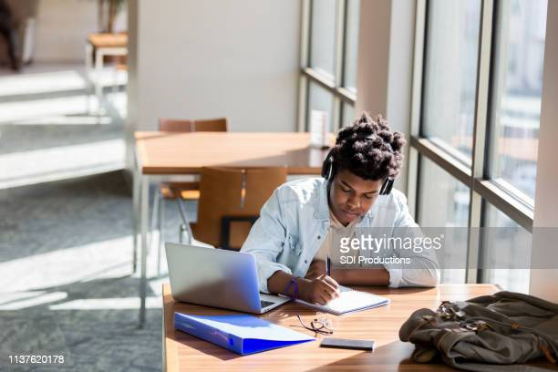 teenage boy studies in de schoolbibliotheek - studerende stockfoto's en -beelden