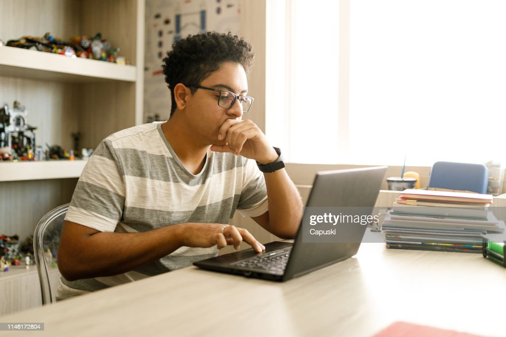 Teenage boy studying with laptop at home : Stock Photo
