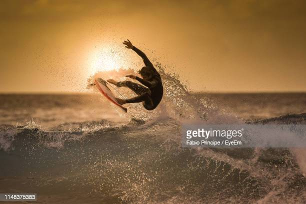 teenage boy surfing in sea against sky during sunset - surf ストックフォトと画像