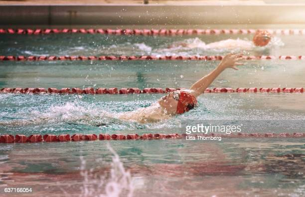 Teenage Boy Swimming Backstroke at a High School Swim Meet