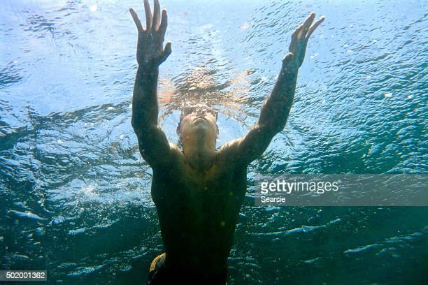 Teenage boy swimming in the ocean doing breastwork