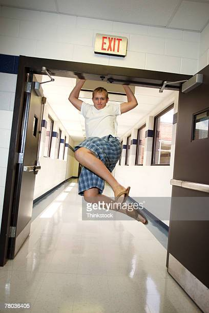 Teenage boy swinging from doorjamb
