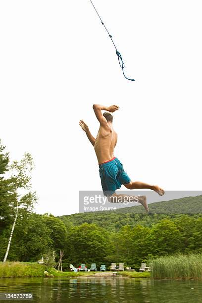Teenage boy swinging off a rope into a lake
