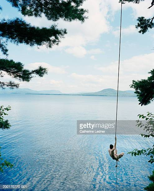 teenage boy swinging over lake on rope swing, rear view - moosehead lake stock photos and pictures