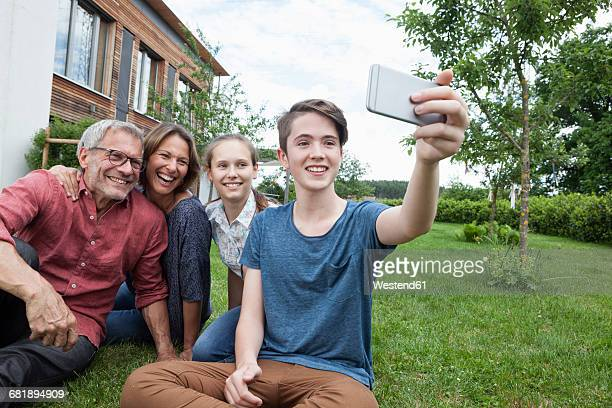 Teenage boy taking a selfie of happy family sitting in garden