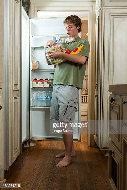 teenage boy taking food from fridge - teen boy barefoot stock photos and pictures
