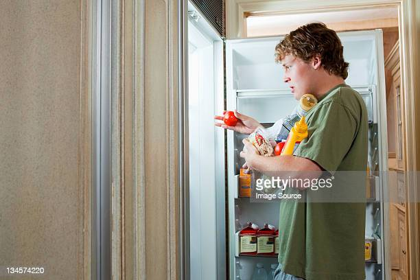 teenage boy taking food from fridge - over eating stock pictures, royalty-free photos & images