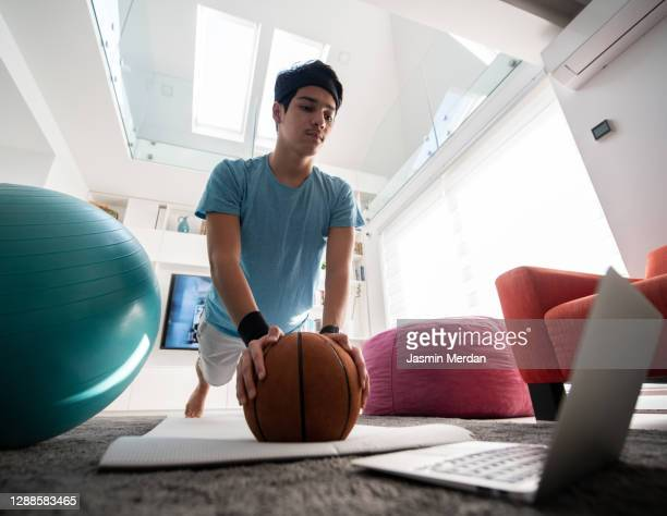 teenage boy taking online sport lessons during lockdown in isolation - turner syndrome stock-fotos und bilder