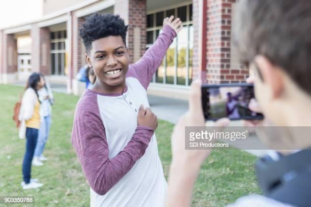 Teenage boy taking photo outside high school on campus