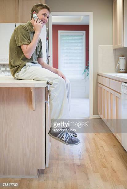 Teenage boy (14-15) talking on mobile, sitting on counter, side view