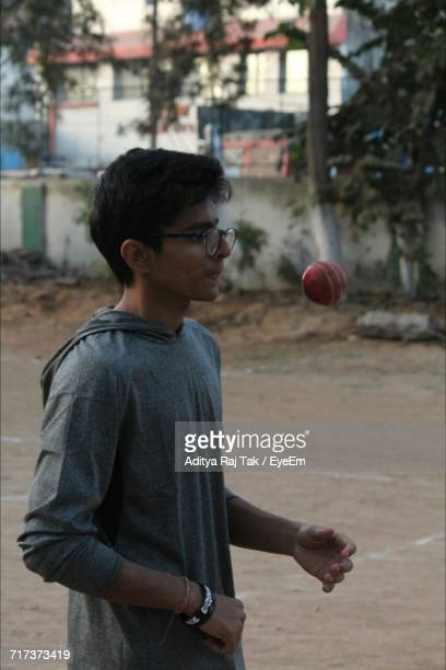 Teenage Boy Tossing Ball While Playing Cricket