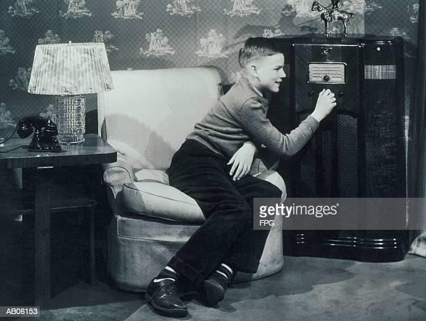 teenage boy (13-15) tuning radio (b&w) - siglo xx fotografías e imágenes de stock