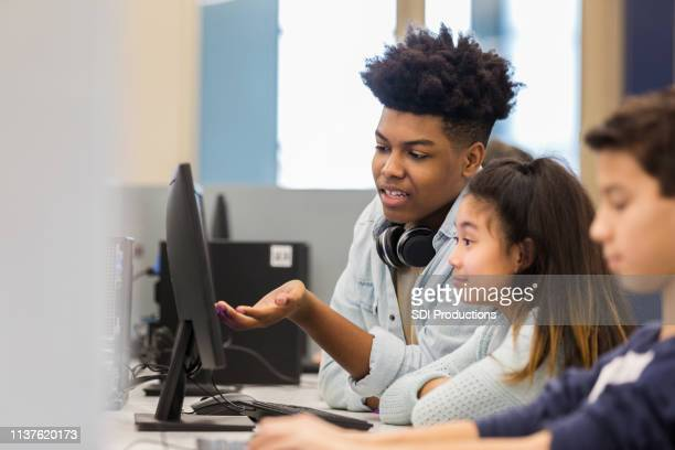 teenage boy tutors elementary school student - science photo library stock pictures, royalty-free photos & images