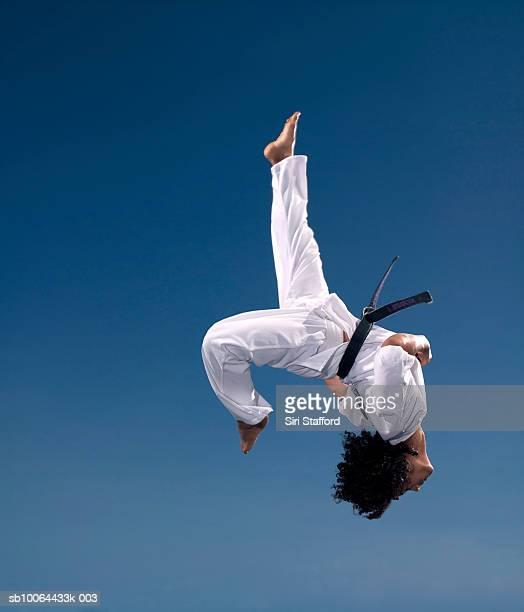 Teenage boy (14-15) upside down in mid-air, low angle view