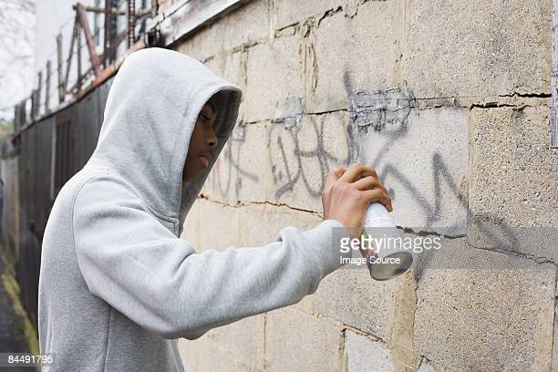A teenage boy using a spray can