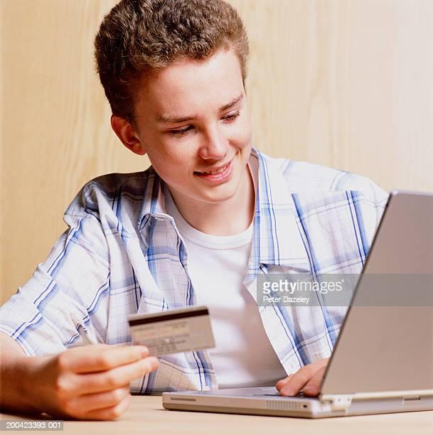 Teenage boy (15-17) using laptop and holding bank card, smiling