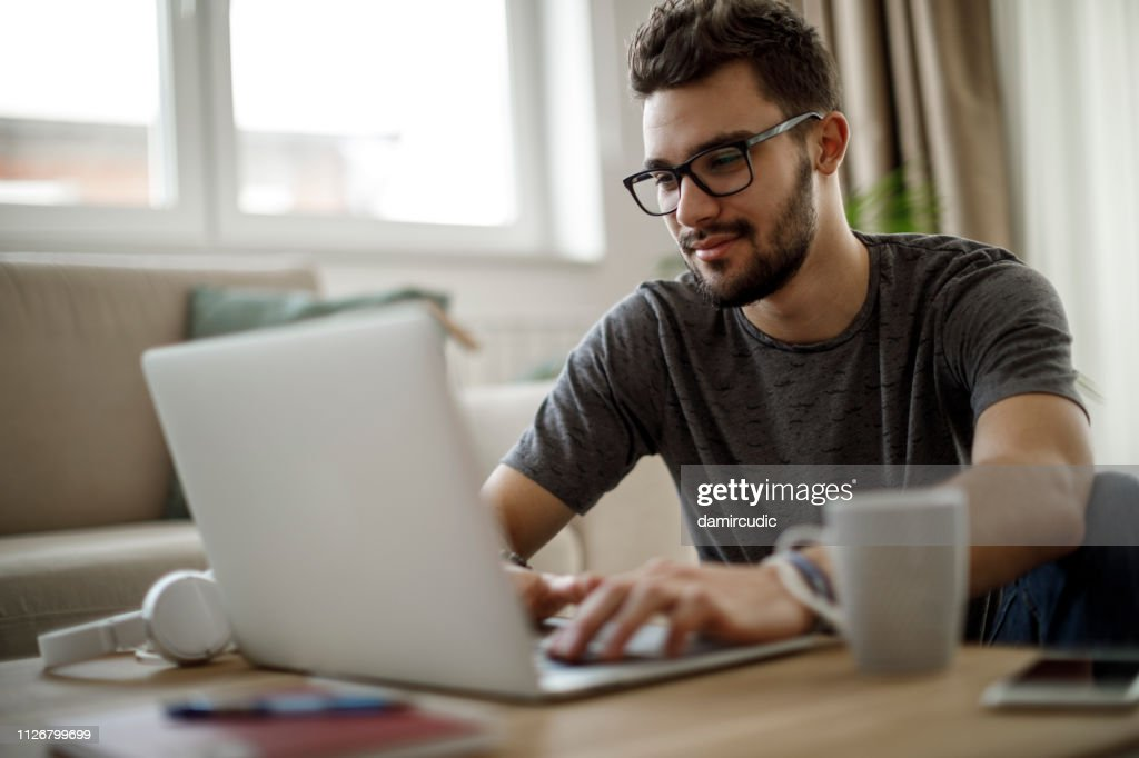 Adolescente usando o laptop em casa : Foto de stock