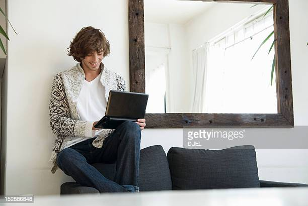 Teenage boy using laptop on sofa