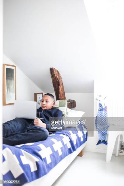 Teenage boy using laptop while lying on bed at home